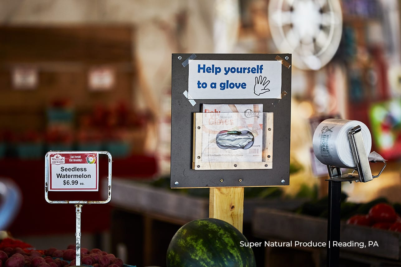sign saying 'help yourself to a glove' at super natural produce store in reading, pa